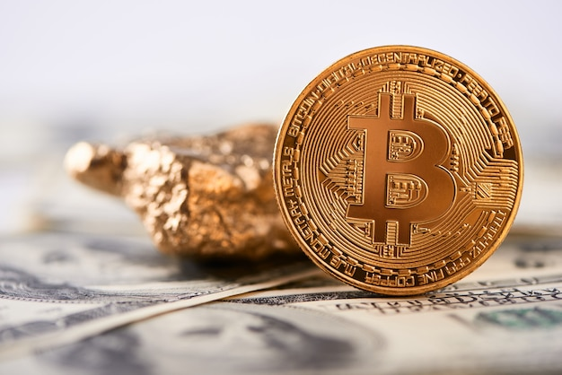 Shiny golden bitcoin and gold lump put on dollar banknote and represent new financial trends.