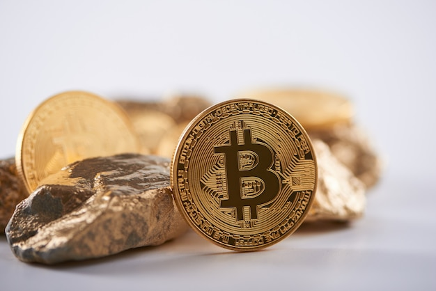 Shiny golden bitcoin next to lumps of gold