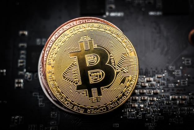 Блестящий золотой биткойн на вершине стопки из бронзового и серебряного биткойна на компьютерной плате