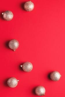 빨간색 배경에 혼란스러운 순서로 빛나는 황금 크리스마스 싸구려, 복사 공간, 최소한의 평면 배치, 텍스트 공간