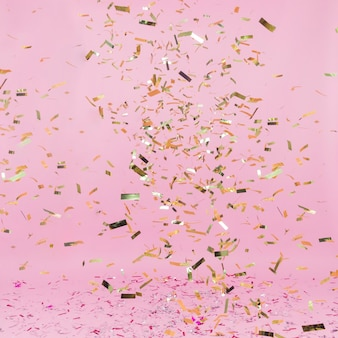Shiny golden confetti falling on pink background