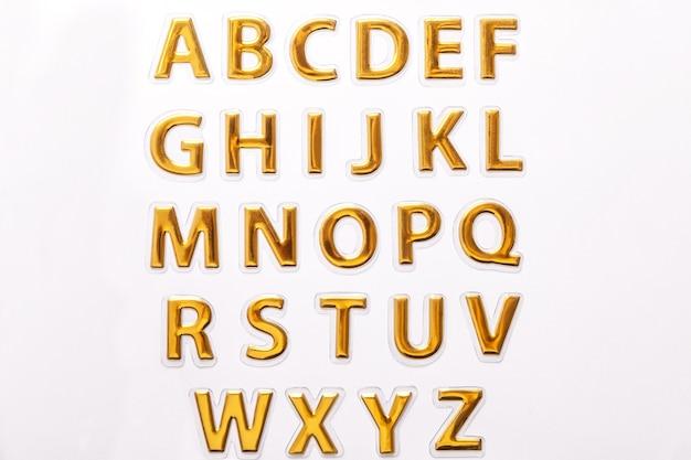 白で隔離される光沢のある黄金の手紙