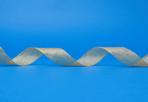 Shiny golden satin ribbon on blue