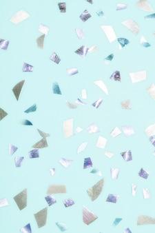 파스텔 블루 배경 테라조 스타일의 반짝이는 금속 색종이 조각