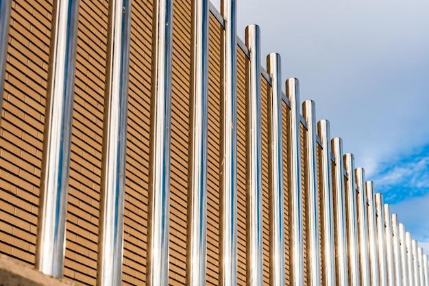 키가 크고 튼튼한 반짝이는 평행 금속 막대가 보안 울타리를 형성합니다.