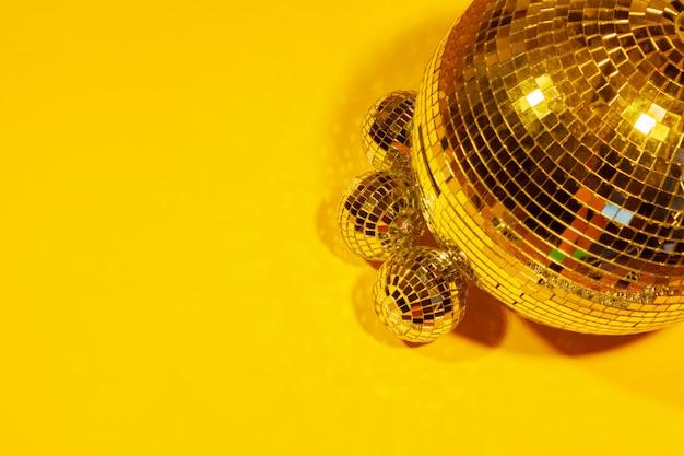 Shiny party disco balls shining on yellow
