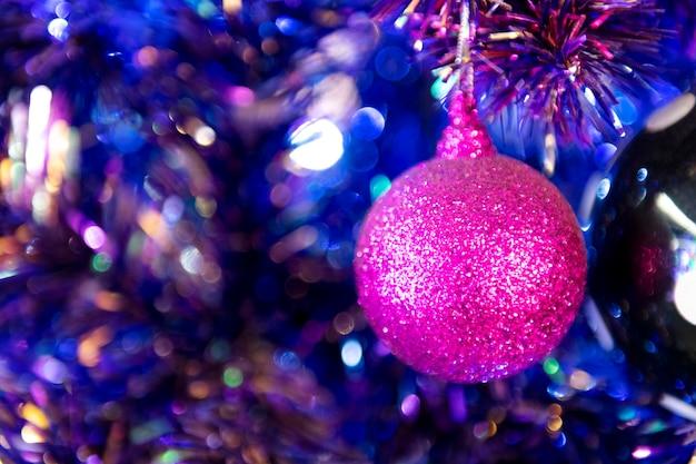 Блестящий розовый рождественский шар висит