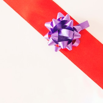 Shiny purple ribbon on red striped over white background