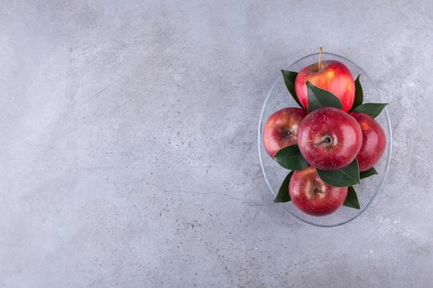 Блестящие красные яблоки с зелеными листьями на каменном фоне.