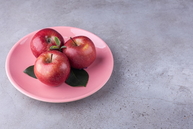 Блестящие красные яблоки с зелеными листьями на камне.