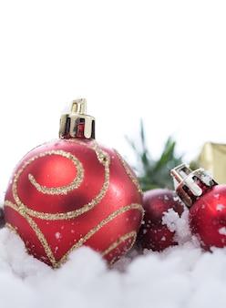 雪の上の光沢のある赤いクリスマスボールとギフトボックス