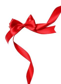 光沢のある赤いサテンのリボンと白で隔離の弓