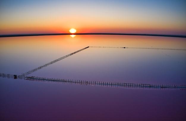 Shiny salty pink lake and a path along it