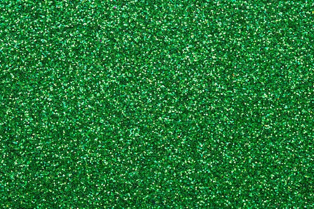 Shiny sequin fabric. sparkle green texture, dark glitter background. shimmering surface of textile
