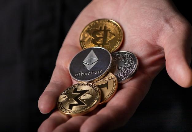 黒の背景の上の男性の手のひらの暗号通貨の光沢のあるシルバーとゴールドのコイン、クローズアップ。イーサリアム、モネロ、ビットコイン、その他の暗号通貨の山。