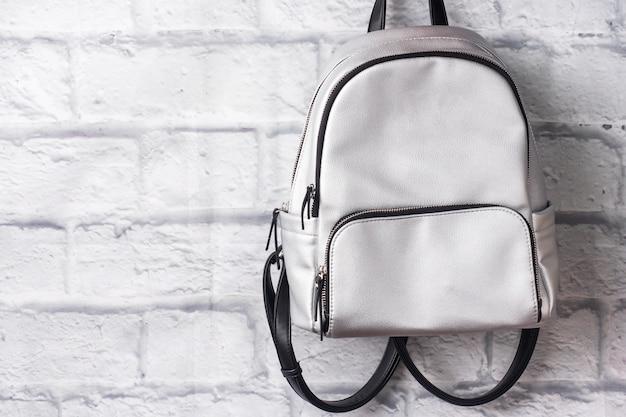 Блестящий серебряный рюкзак на фоне кирпичной стены. копировать пространство
