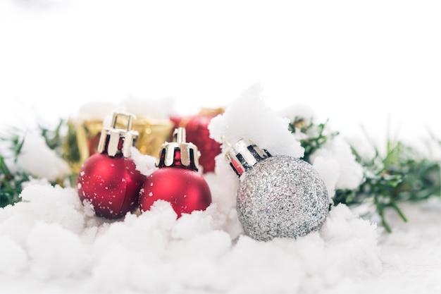 雪の上の光沢のあるシルバーのクリスマスボールギフトボックス