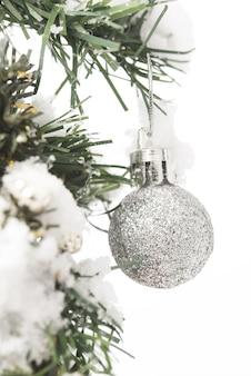 雪の上の光沢のあるシルバーのクリスマスボール