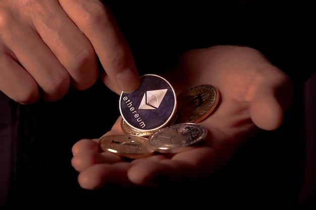 黒の背景の上の男性の手のひらの暗号通貨の光沢のある銀のイーサリアムコイン、クローズアップ。 ethは暗号の山に入れます。