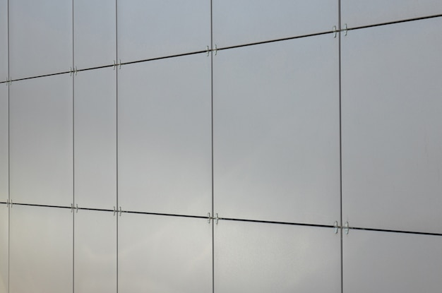 Блестящая гладкая чистая серая квадратная плитка на стене