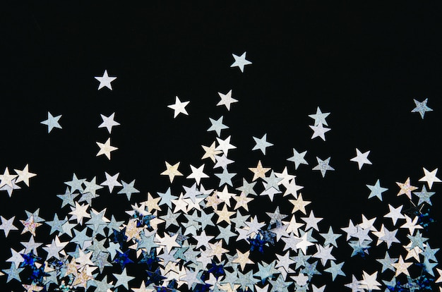 Shiny stars of foil on black background.