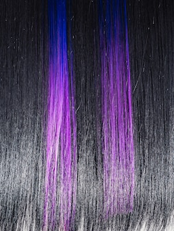 Shiny straight black hair background. beautiful smooth brunette hair with colored purple lilac blue strands. beauty trend
