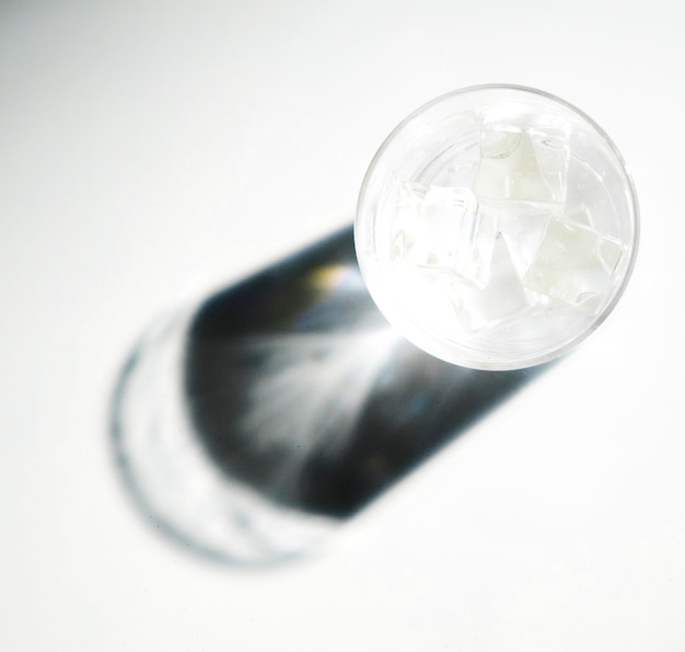 Shiny sunlight on the dark shadow of glass with ice cubes on white background