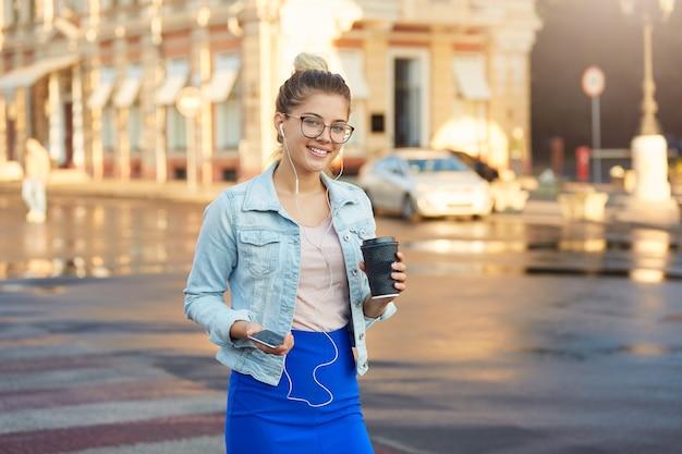 メガネでかなり金髪の若い女性の光沢のある日当たりの良い屋外写真はデニムジャケットと青いスカートで街を歩く