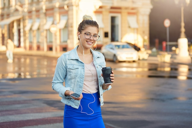 Shiny sunny outdoor photo of pretty blonde young woman in glasses walks around the city in a denim jacket and blue skirt