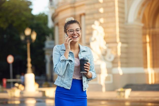 Foto all'aperto soleggiata lucida di bella giovane donna con gli occhiali cammina per la città in una giacca di jeans e gonna blu, beve caffè