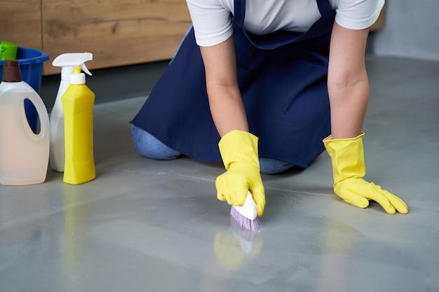 光沢のある表面。自宅で洗剤で床を掃除する黄色い手袋で若い女性の手のクローズアップ。家事とハウスキーピング、クリーニングサービスのコンセプト