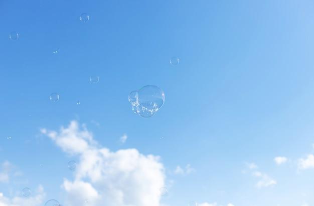 Блестящие прозрачные мыльные пузыри против голубого неба свобода летней концепции
