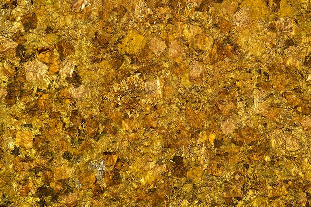 Shiny yellow gold leaf or scraps of gold foil background texture