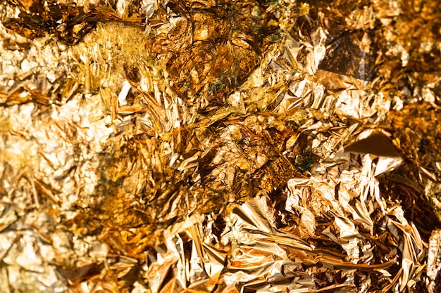 Shiny yellow gold leaf or scraps of gold foil scene