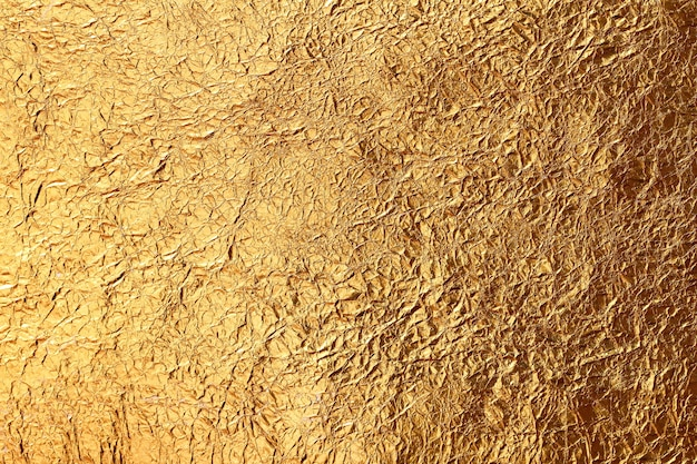 Блестящий желтый лист золотой фольги текстуры фона