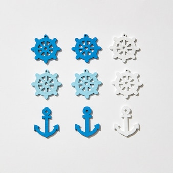Ship anchors and wheel different colors pattern on a light grey with hard shadows, copy space. flat lay