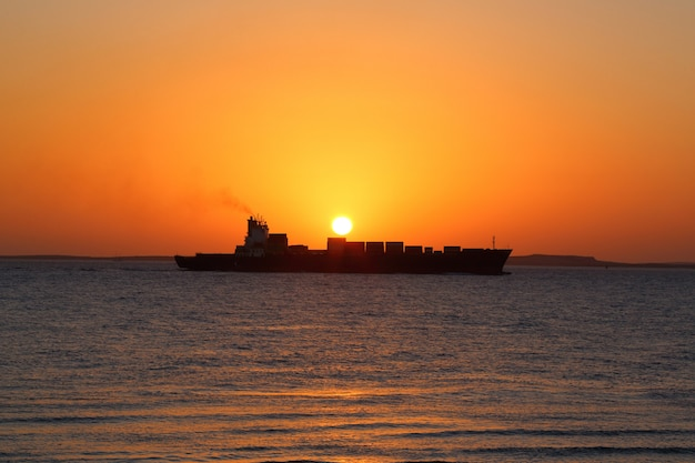 Ship on the background of the golden sunrise