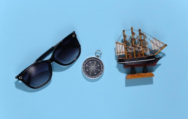 밝은 파란색에 입상, 선글라스 및 나침반을 발송하십시오. 여행, 모험 테마.