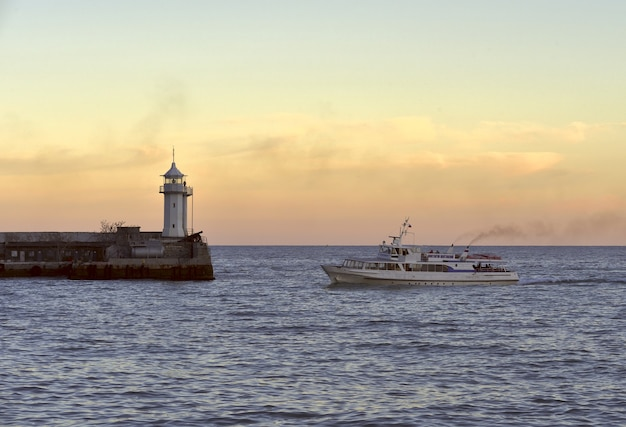 Ship and lighthouse in yalta ship and lighthouse at yalta sea station early in the morning
