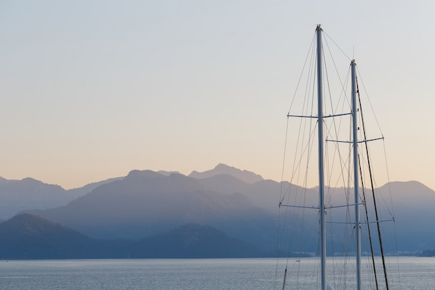 Ship mast on blue sunset sky and mountains.