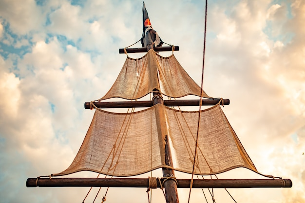 Ship mast with beige sails swings against a blue sky
