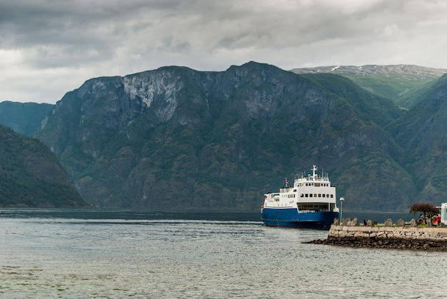 Ship near the pier in the aurlandsfjord fjord. it is a fjord in sogn og fjordane county, norway, a branch of the main sognefjorden. length 29 km