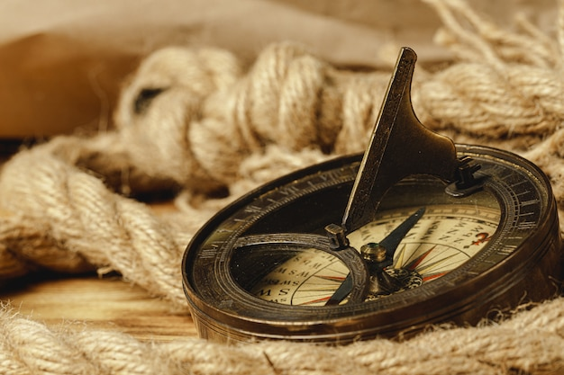 Ship rope and compass on wooden table, close up