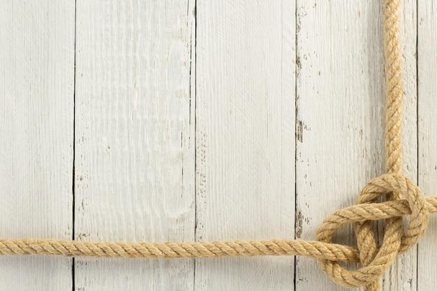 木製の背景にロープを出荷します。