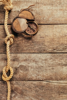 Ship ropes and compass on wooden background