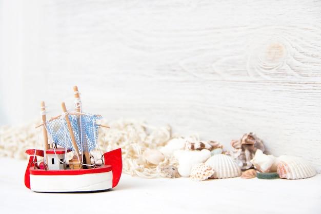 Корабль игрушек и морских раковин и ne на белой деревянной стене крупным планом