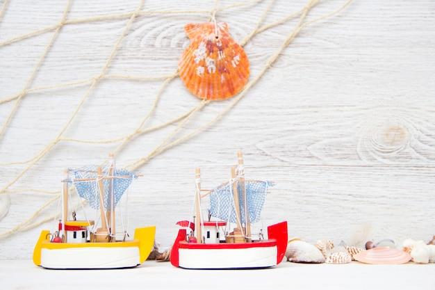 Корабль игрушки и морские раковины и пе на белой деревянной стене крупным планом