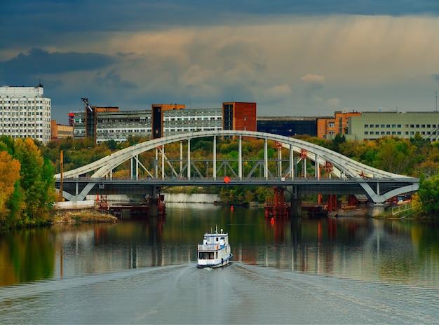 Корабль под мостом на фоне транспорта москвы
