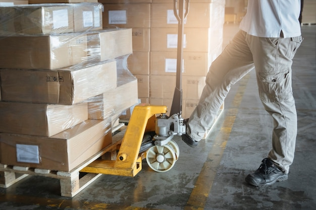 Shipment boxes, delivery service. worker with hand pallet truck unloading cardboard boxes or goods in cargo warehouse.