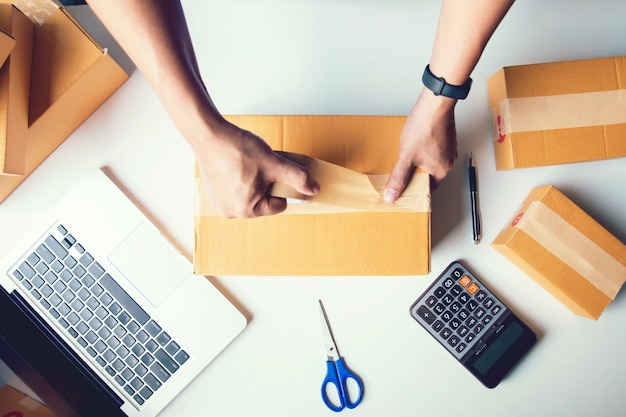 Shipment online sales .man worker delivery service and working packing box, business owner working checking order to confirm before sending customer in post.top view